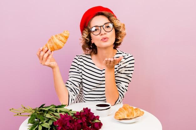 Retrato interior de elegante mujer francesa en boina roja mujer en espectáculos sopla dulce beso y sosteniendo cruasanes.
