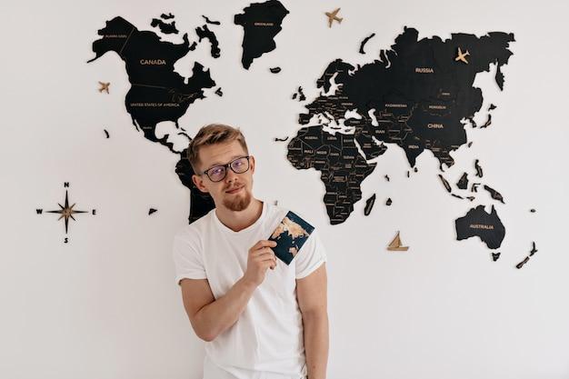 Retrato interior de feliz joven europeo con pasaporte posando sobre el mapa del mundo. preparándose para viajar, viaje de vacaciones.