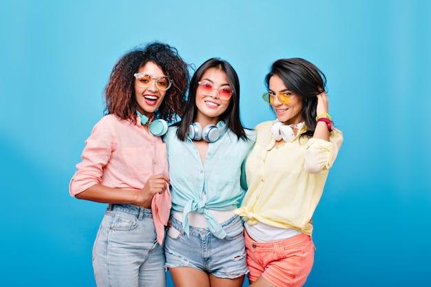 Retrato interior de grupo de fascinantes amigos internacionales con atuendos coloridos y gafas de sol brillantes. señoras morenas sonrientes de diferentes etnias posando juntas.