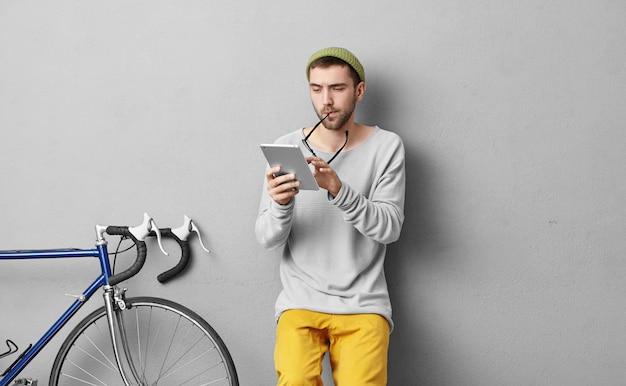 Retrato interior de guapo estudiante leyendo lectura atentamente en tableta moderna, quitándose gafas, participando en el estudio