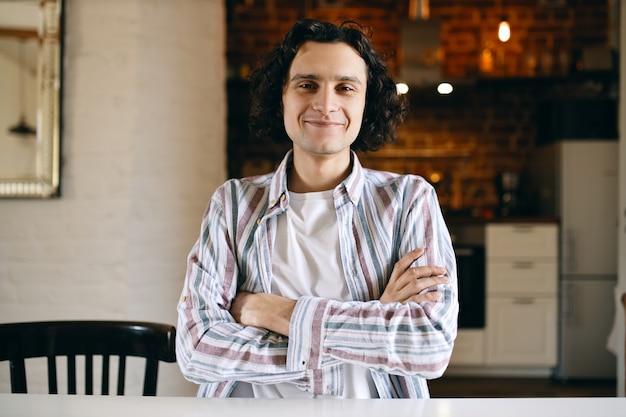 Retrato interior de guapo feliz entusiasta chico en camisa a rayas sentado en la mesa de la cocina con los brazos cruzados