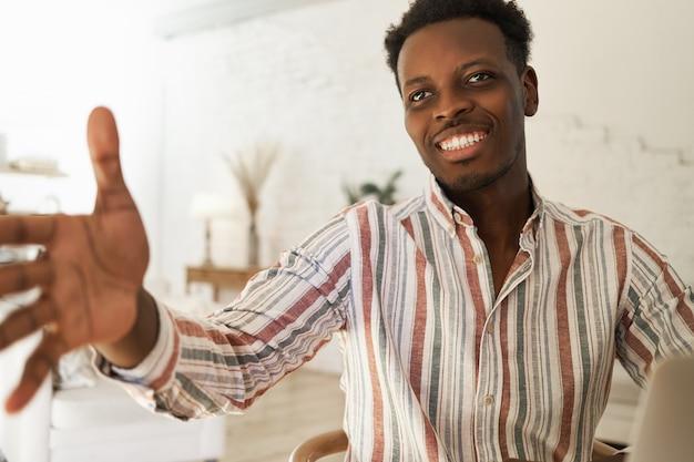 Retrato de interior de guapo joven africano confiado en camisa a rayas con expresión facial amistosa