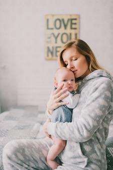 Retrato interior de hapy joven en pijama sosteniendo, abrazando a su bebé recién nacido cerca de la pared con placa decorativa. la madre cuida a su hijo pequeño. concepto de maternidad el amor es todo lo que necesitas