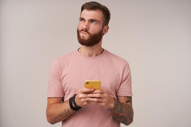 Retrato interior de un joven desconcertado, sin afeitar, morena, con corte de pelo de moda, sosteniendo el teléfono móvil con estuche amarillo y mirando hacia arriba pensativamente, aislado en blanco