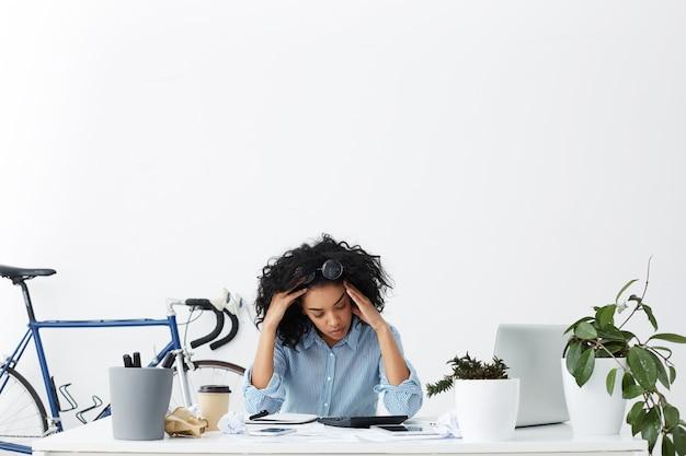Retrato interior de la joven empresaria cansada con exceso de trabajo sintiéndose estresada