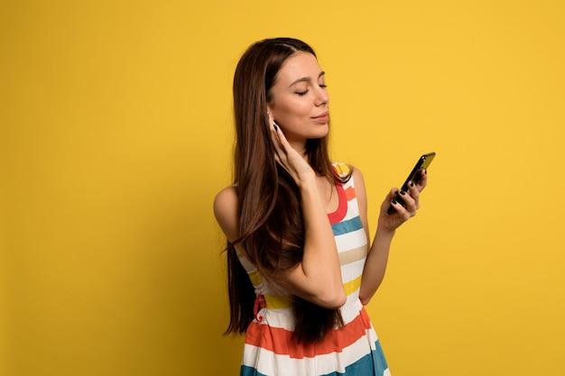 Retrato interior de una joven encantadora con cabello largo y oscuro está escuchando música y mirando el teléfono sobre la pared amarilla