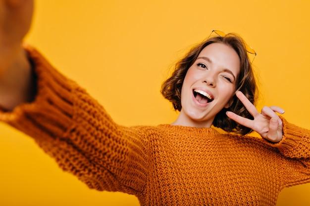 Retrato interior de mujer dichosa en ropa tejida haciendo selfie y riendo sobre fondo brillante