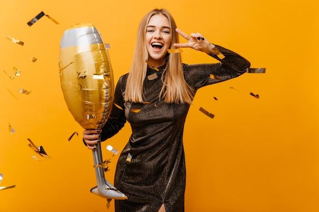 Retrato interior de mujer encantadora riendo con copa de vino posando en amarillo. hermosa mujer de cumpleaños en vestido de pie bajo confeti y riendo.
