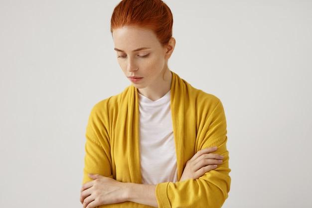 Retrato interior de mujer hermosa pelirroja con capa amarilla, manteniendo las manos cruzadas, mirando hacia abajo con expresión triste, pensando en algo. mujer con cabello pelirrojo y mirada segura