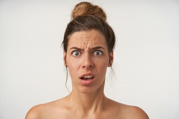 Retrato interior de una mujer joven aturdida con la cara con los ojos abiertos, la frente arrugada con la boca abierta, posando en blanco sin maquillaje