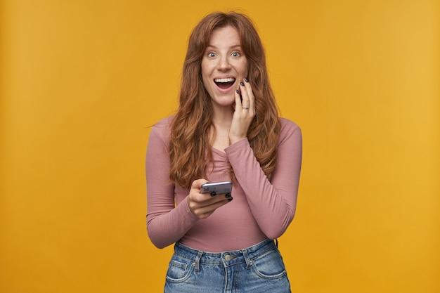 Retrato de interior de mujer joven de jengibre, sonríe con cabello ondulado y pecas mientras sostiene el teléfono con expresión facial sorprendida.
