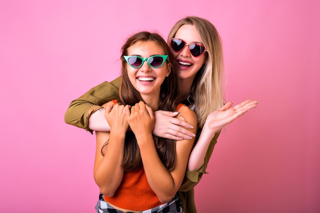 Retrato interior positivo alegre de dos divertidos abrazos de mujer rubia y morena y mirando el uno al otro