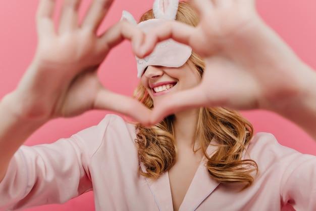 Retrato de interior de una romántica chica rubia en antifaz posando con signo de amor. linda mujer joven y bonita en pijama y antifaz para dormir divirtiéndose en su habitación.
