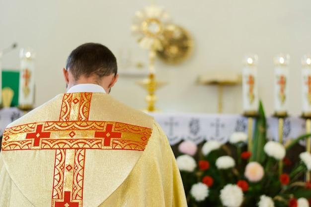 Retrato interior del sacerdote católico desde atrás