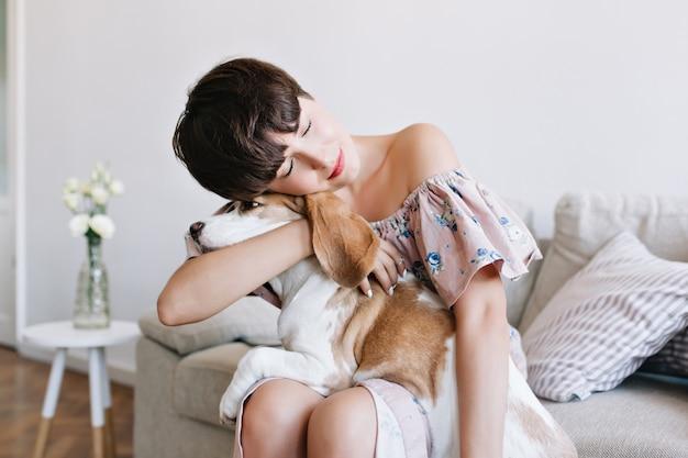 Retrato interior de una soñadora niña de pelo castaño en traje vintage abrazando perro beagle con los ojos cerrados