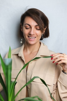 Retrato interior suave de mujer caucásica suave con traje beige sin sujetador, posando detrás de una planta tropical de palma, gris.