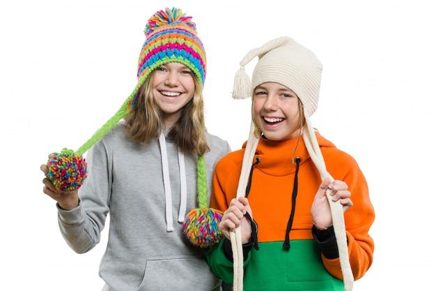 Retrato de invierno de dos niñas sonrientes felices en sombreros de punto