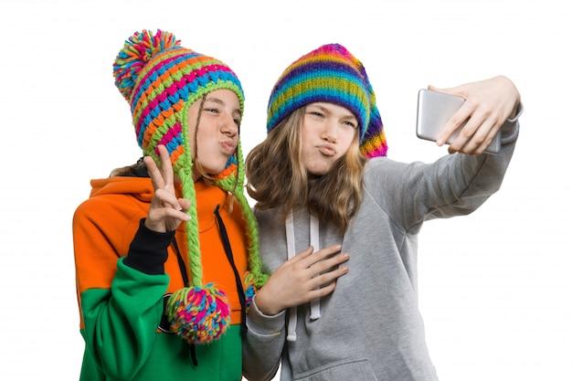 Retrato de invierno de dos novias adolescentes hermosas felices en sombreros de punto