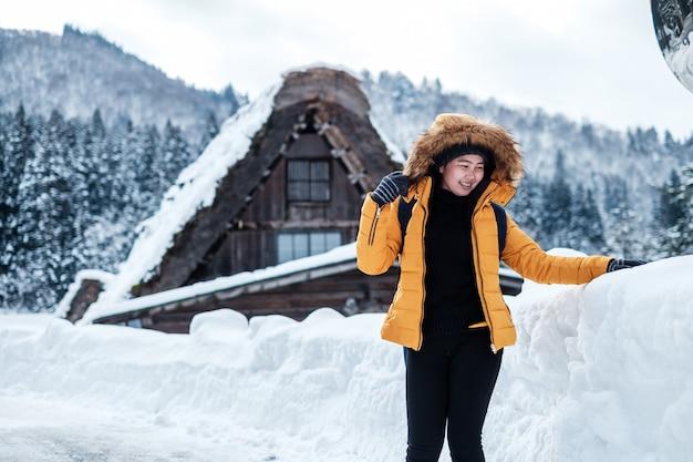 Retrato de invierno de joven bella mujer asiática en la nieve. concepto de moda de belleza de invierno nevando