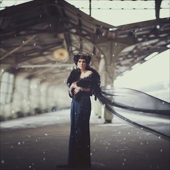 Retrato de invierno de moda de una hermosa morena con un vestido largo y mehndi en sus manos en el edificio de la antigua estación de tren. maquillaje creativo y peinado