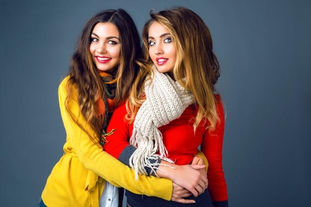 Retrato de invierno de moda de rubias y morenas hermosas chicas mejores amigas, abrazos y diversión. usar suéteres y bufandas de cachemira con estilo brillante. ten un maquillaje moderno y cabellos largos increíbles.