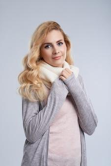 Retrato de invierno de mujer caucásica envolviendo en cálida bufanda de lana