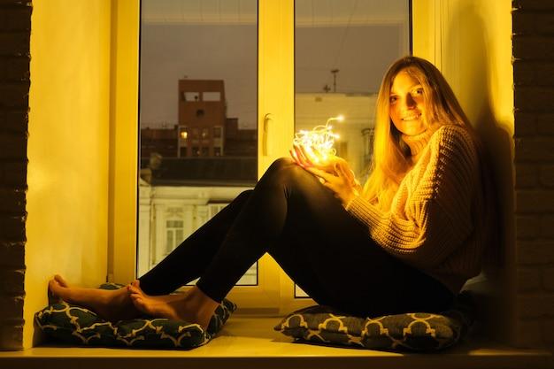 Retrato de invierno de mujer hermosa joven sentada junto a la ventana en el alféizar de la ventana, fondo de la ciudad de noche, luces de guirnalda brillantes en manos de la niña