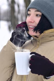 Retrato de invierno de niña con smartphone y taza de café