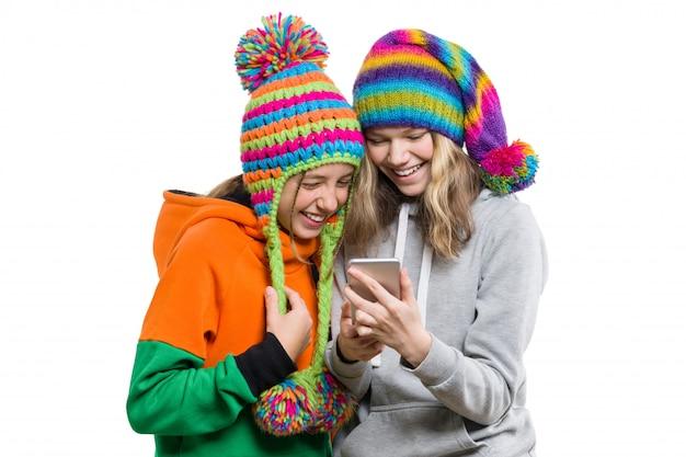 Retrato de invierno de niñas felices en sombreros de punto