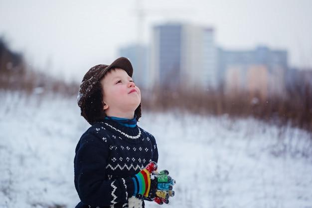 Retrato de invierno de niño niño con un suéter de punto con ciervos, al aire libre durante las nevadas.