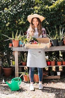 Retrato de un jardinero femenino con sombrero sosteniendo la planta en maceta seleccionada en la cesta