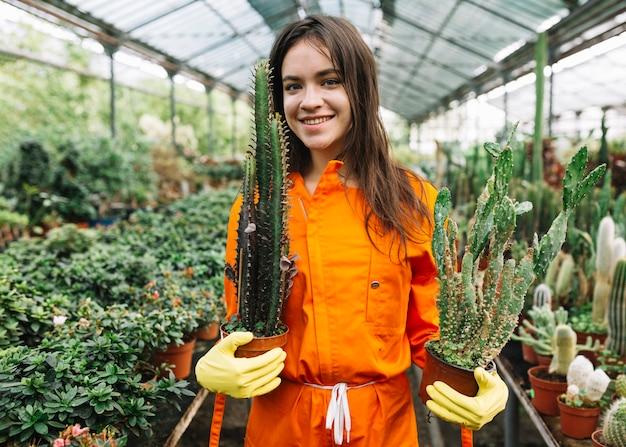 Retrato de un jardinero de sexo femenino joven sonriente que sostiene las plantas en conserva del cactus