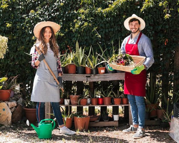 Retrato de un jardinero de sexo femenino y masculino que sostiene la cesta de las plantas de la azada y del potted en el jardín
