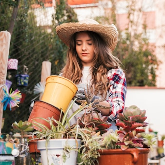Retrato de un jardinero de sexo femenino que lleva el sombrero que mira el pote floreciente vacío