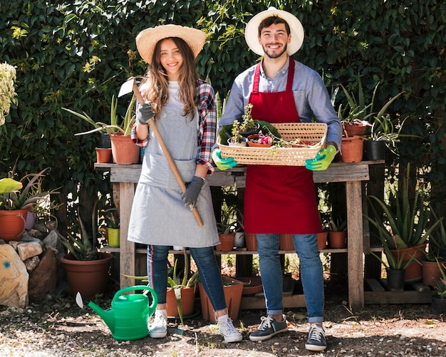 Retrato del jardinero de sexo masculino y de sexo femenino que sostiene herramientas y la cesta en el jardín