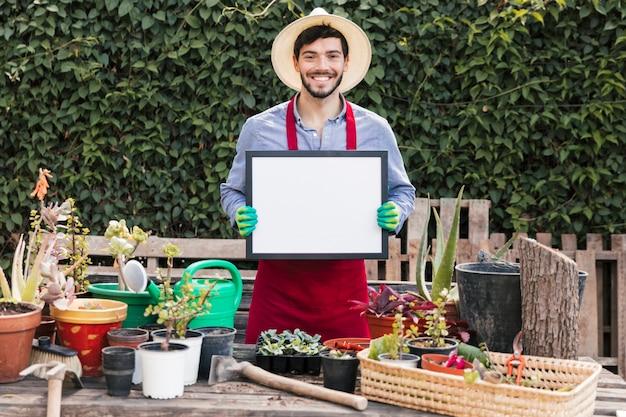 Retrato de un jardinero de sexo masculino sonriente que lleva a cabo el marco blanco delante de las plantas en conserva en la tabla