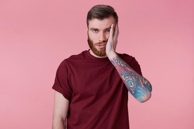 Retrato de joven aburrido triste con la mano tatuada, apoyando la cabeza, aislado sobre fondo rosa.