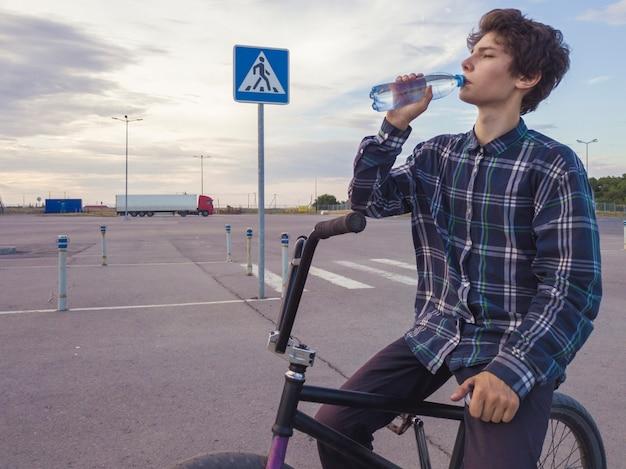 Retrato de joven adolescente bebiendo agua embotellada sentado en bicicleta bmx