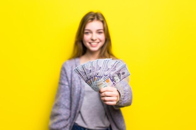 Retrato de una joven adolescente casual sosteniendo billetes de dinero aislado