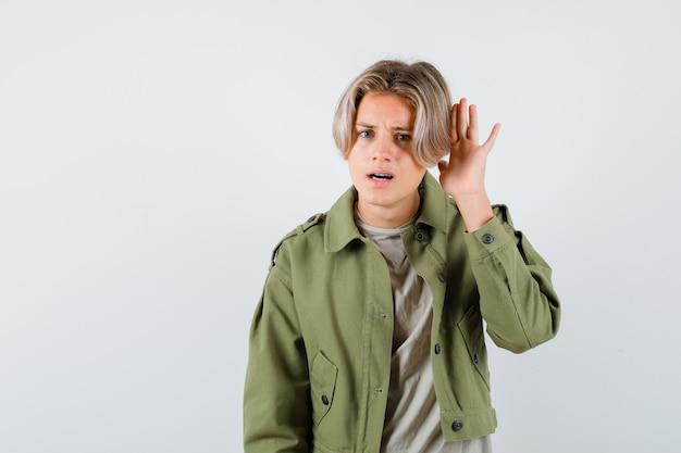 Retrato de joven adolescente con la mano detrás de la oreja en chaqueta verde y mirando confundido vista frontal