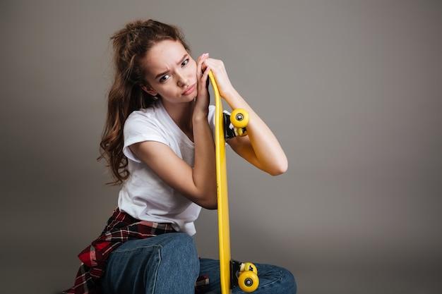 Retrato de una joven adolescente sentada con patineta