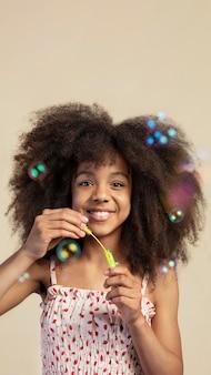 Retrato de joven adorable posando mientras juega con pompas de jabón