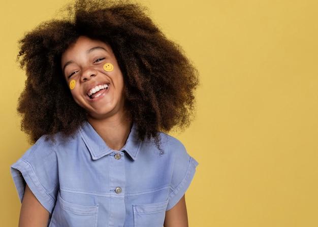 Retrato de joven adorable posando con pegatinas emoji en su rostro