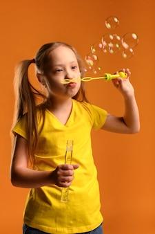 Retrato de joven adorable soplando burbujas