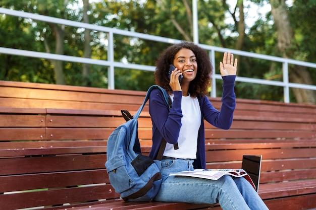 Retrato de una joven africana feliz con mochila hablando por teléfono móvil mientras descansa en el parque, leyendo una revista, agitando la mano