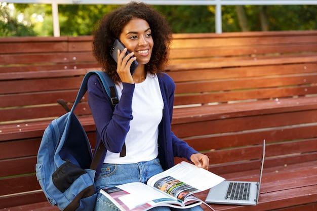 Retrato de una joven africana feliz con mochila hablando por teléfono móvil mientras descansa en el parque, leyendo una revista