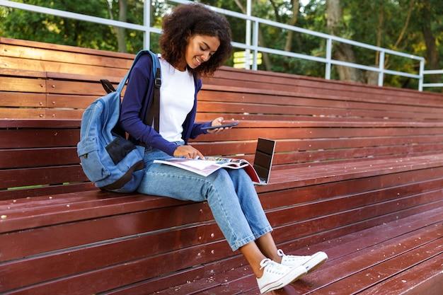 Retrato de una joven africana feliz con mochila mediante teléfono móvil mientras descansa en el parque, leyendo una revista
