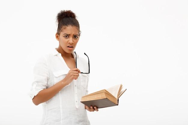 Retrato de joven africana con libro sobre pared blanca