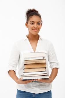 Retrato de joven africana con libros sobre pared blanca
