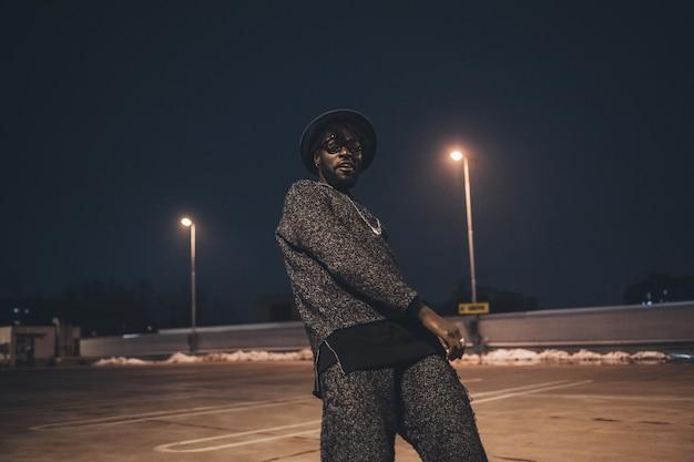 Retrato de joven africano bailando en el espacio de estacionamiento